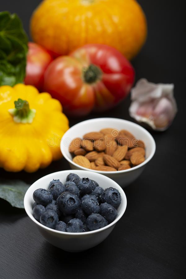Blaubeere mit Wassertropfen in einer Schüssel mit einem Hintergrund des Gemüses, der Frucht und der Nüsse stockbilder