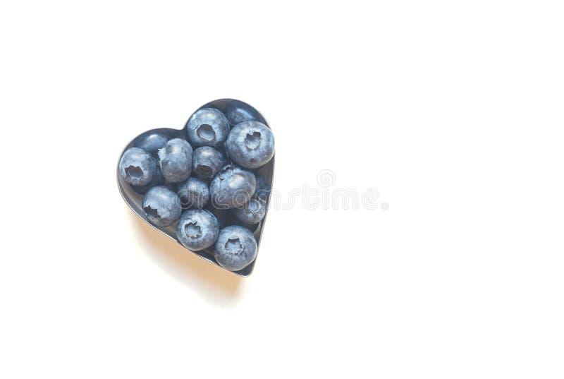 Blaubeeren in Form des Herzens lokalisiert auf weißem Hintergrund stockbild