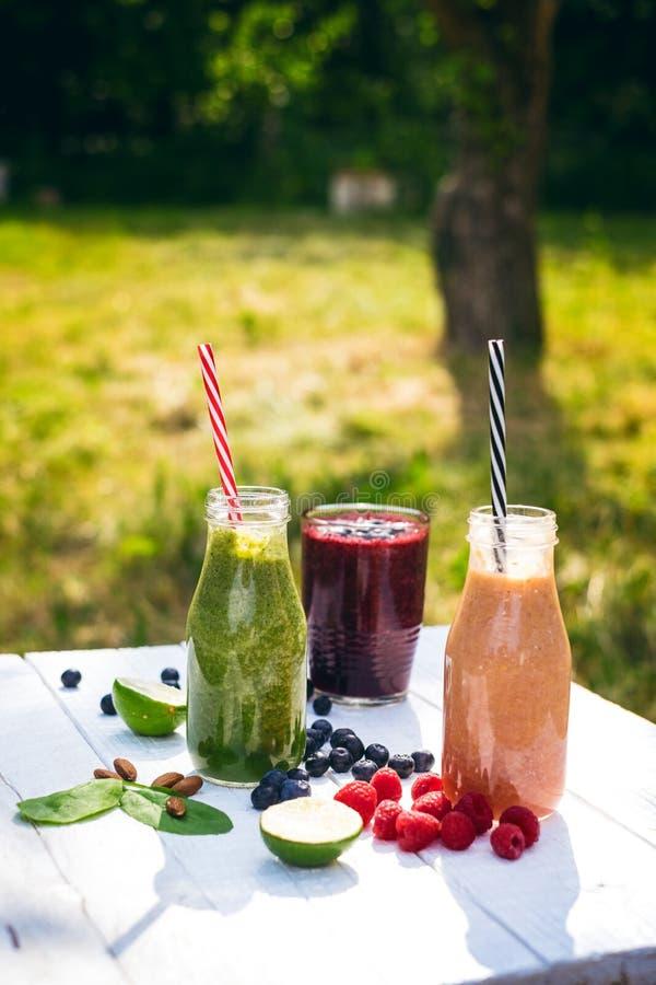 Blaubeeren-, spinachy und Orange Smoothie auf einem hölzernen weißen Hintergrund in der Natur Gläser von Smoothie mit Beere und M stockbilder
