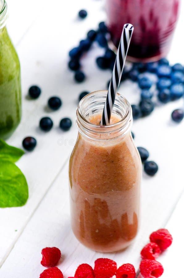 Blaubeeren-, spinachy und Orange Smoothie auf einem hölzernen weißen Hintergrund Gläser von Smoothie mit Beere und Minze Beere, B stockfotos