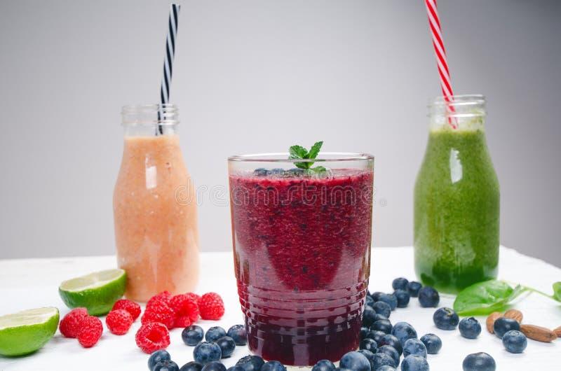 Blaubeeren-, spinachy und Orange Smoothie auf einem hölzernen weißen Hintergrund Gläser von Smoothie mit Beere und Minze Beere, B lizenzfreies stockfoto