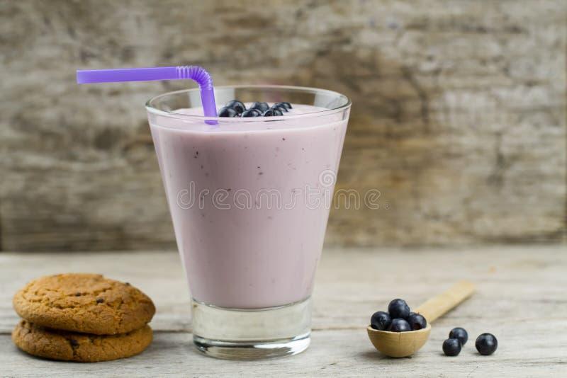 Blaubeerensmoothie mit Beeren, Haferplätzchen auf hölzernem Hintergrund Gesunde vegetarische Nahrung lizenzfreie stockfotos