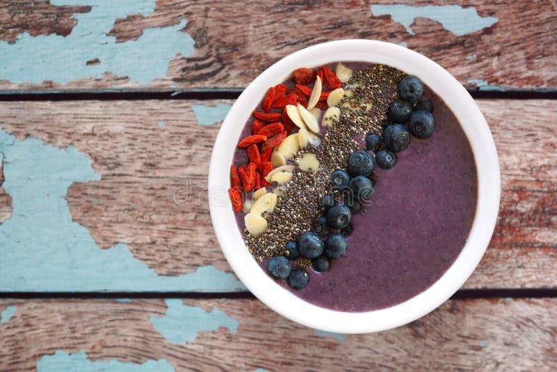 Blaubeerensmoothieschüssel mit superfoods auf rustikalem altem Holz stockfotos