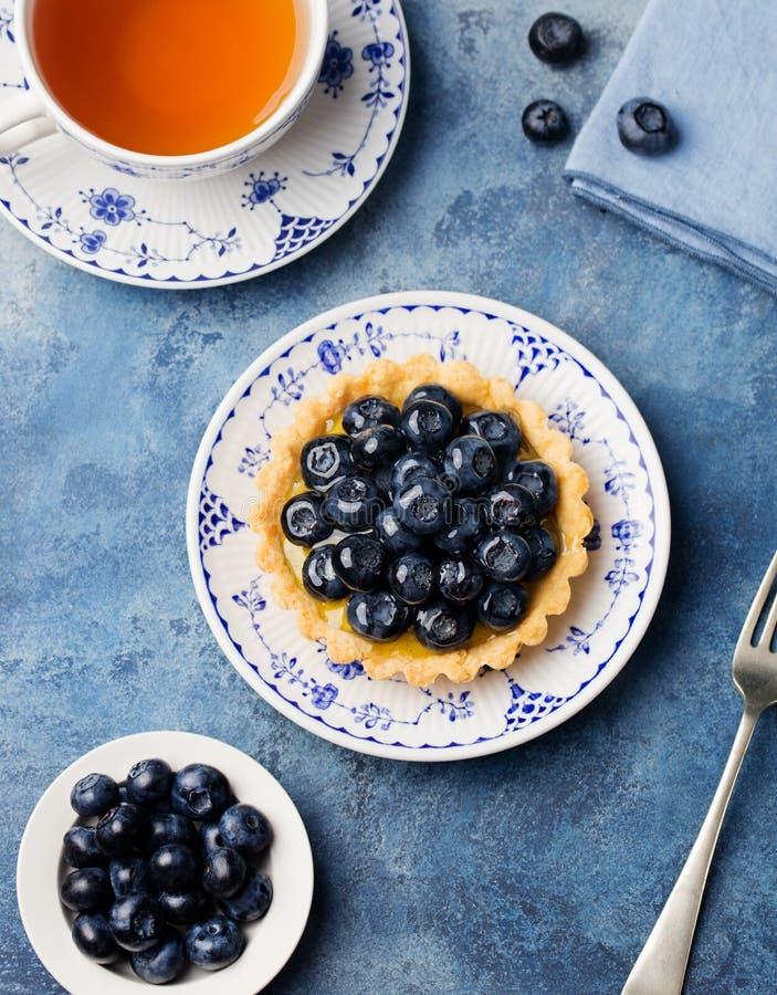 Blaubeerentartlet, Torte, scharf mit Vanillevanillepudding Blauer Stein-Hintergrund stockbild