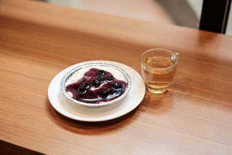 Blaubeerkäsekuchen mit chinesischem grünem Tee und künstliche Anlage auf dem Holztisch stockfotos