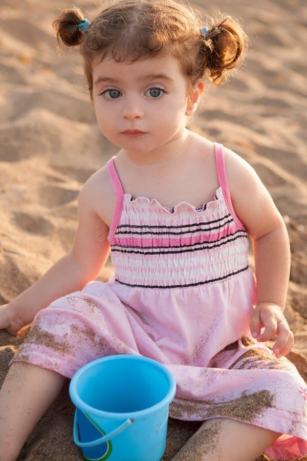 Blaue Augen Brunettekleinkindmädchen, das mit Sand im Strand spielt stockfotografie
