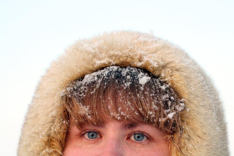 Blaue Augen und Haar der Frau unter Schnee stockfotografie