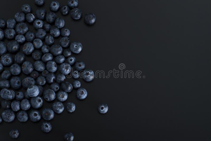 Blaue Beeren lokalisiert auf schwarzem Hintergrund stockbild