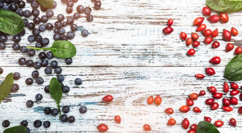 Blaue Beeren und Frucht von Brier mit Basilikumblättern auf hölzernem rustikalem Hintergrund lizenzfreie stockbilder