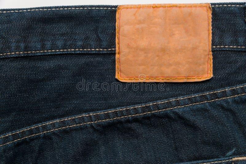 Blaue Denimjeans mit Aufkleber als Hintergrund lizenzfreie stockbilder