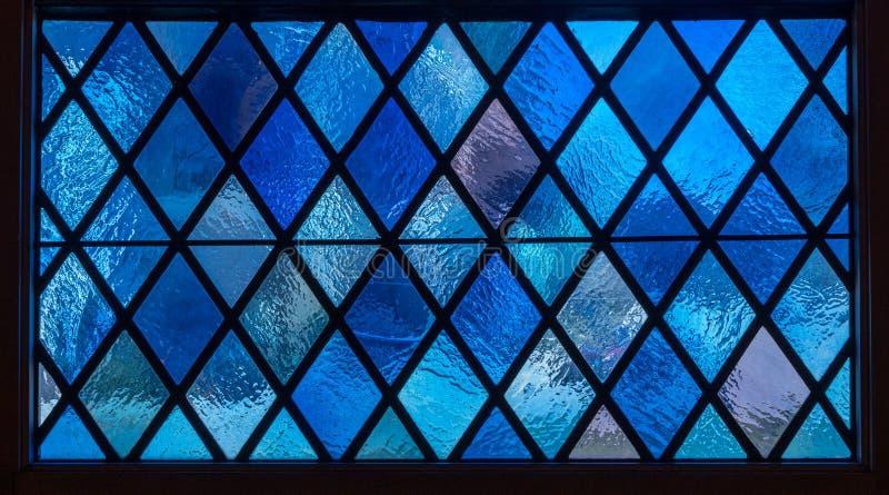 Blaue Diamantscheiben im Buntglasfenster in der amerikanischen katholischen Kirche lizenzfreies stockfoto