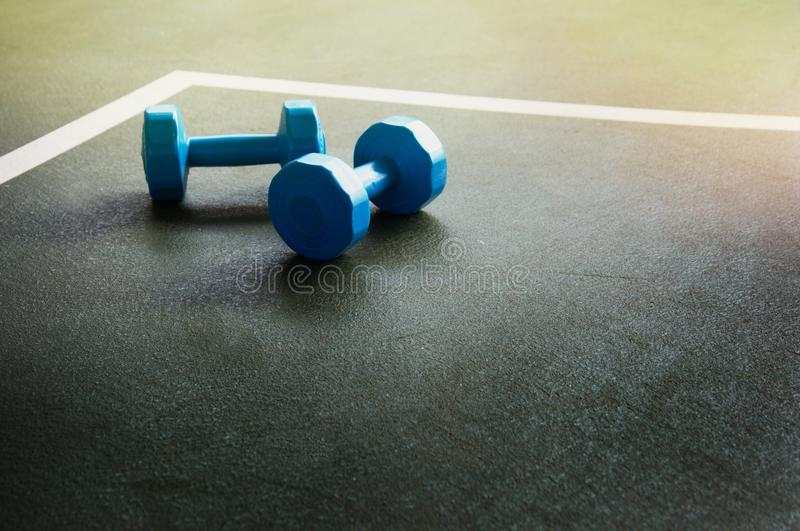 Blaue Dummköpfe für Eignung auf dunkelgrüner Turnhalle des Bodens tragen b zur Schau stockbild