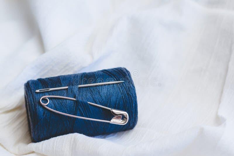 Blaue Fadenspule mit Nähnadel und Stift vom weißen Baumwollstoff lizenzfreies stockbild