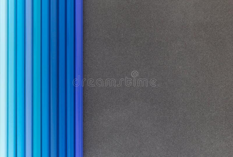 Blaue farbige Bleistifte auf Draufsicht des dunklen Hintergrundes lizenzfreie stockfotografie