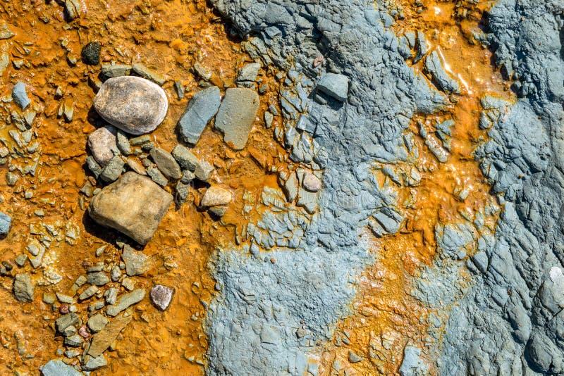 Blaue Felsen mit orangefarbenem Wasser stockbild