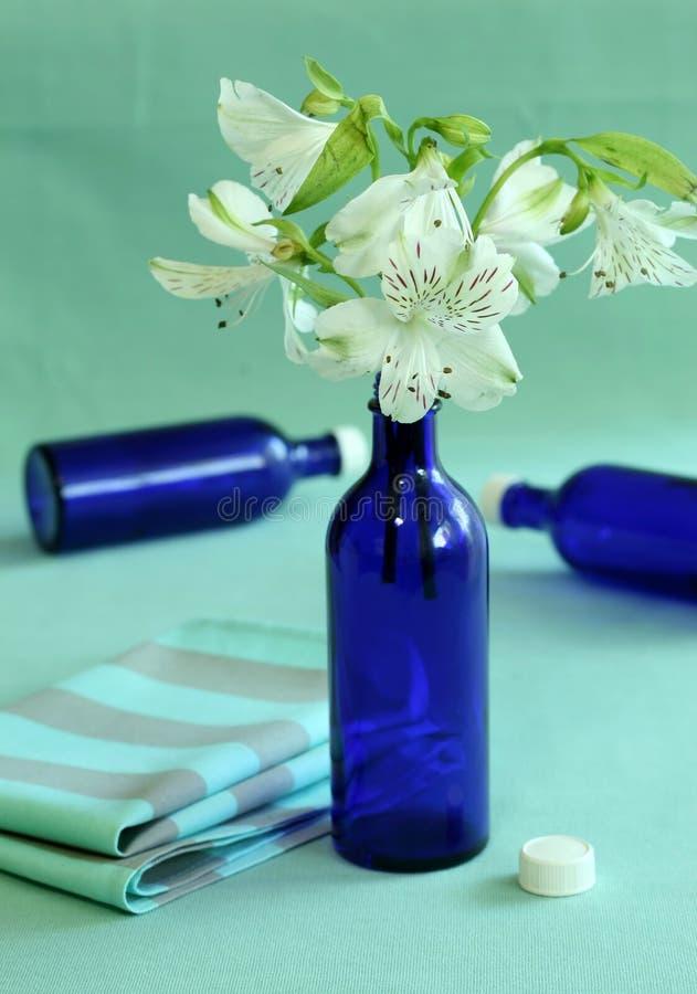Blaue Flaschen und Blumen. lizenzfreie stockfotografie