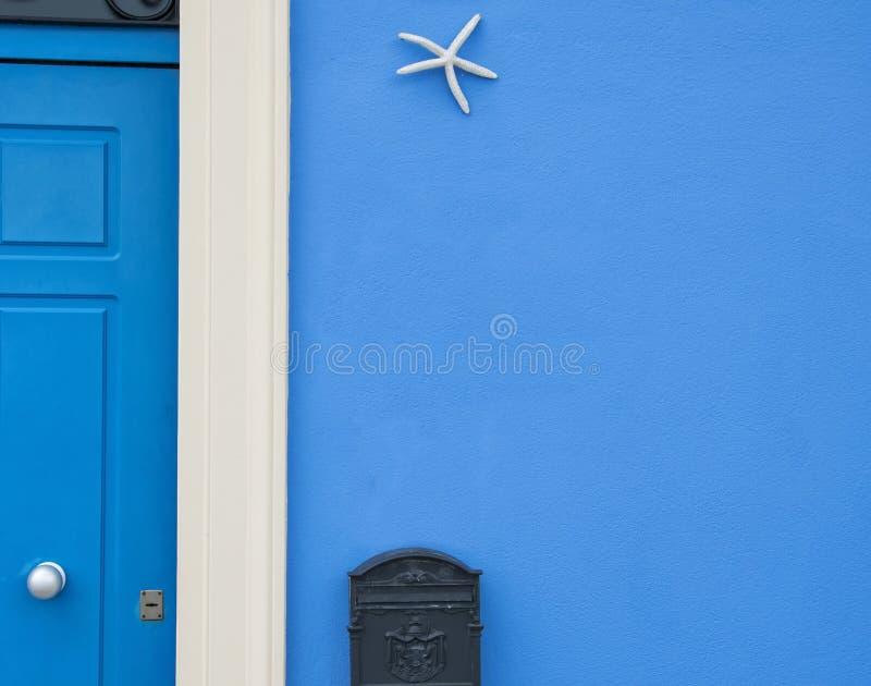 Blaue Gebäudefassade mit Weiß gestalteter Tür lizenzfreie stockfotografie