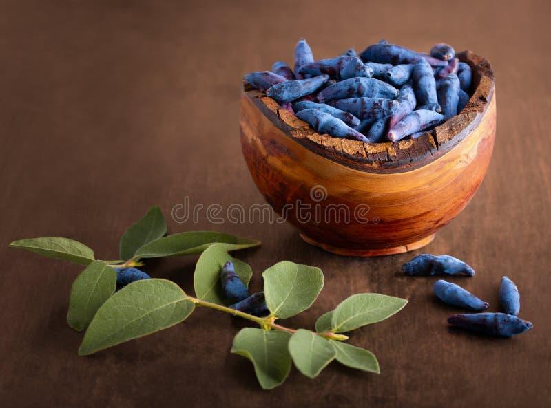 Blaue Geißblattbeeren in einer hölzernen Schüssel, auf einer hölzernen Tischplatte, Geißblattblätter stockfotografie