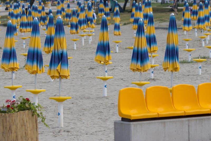 Blaue gelbe Regenschirme warten auf das Öffnen in einem sandigen Strand lizenzfreies stockbild