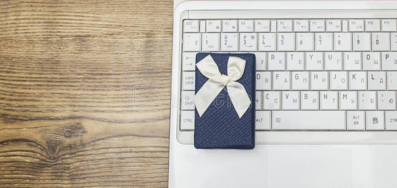 Blaue Geschenkbox und weißer Laptop auf hölzernem Hintergrund stockbild
