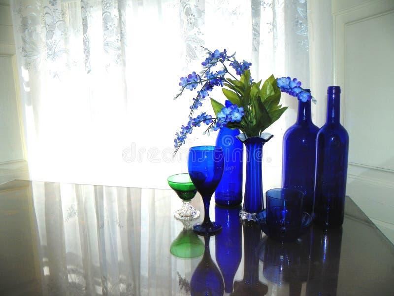 Blaue Glaszusammenstellung auf Glastischplatte vor Spitzefenster stockbilder