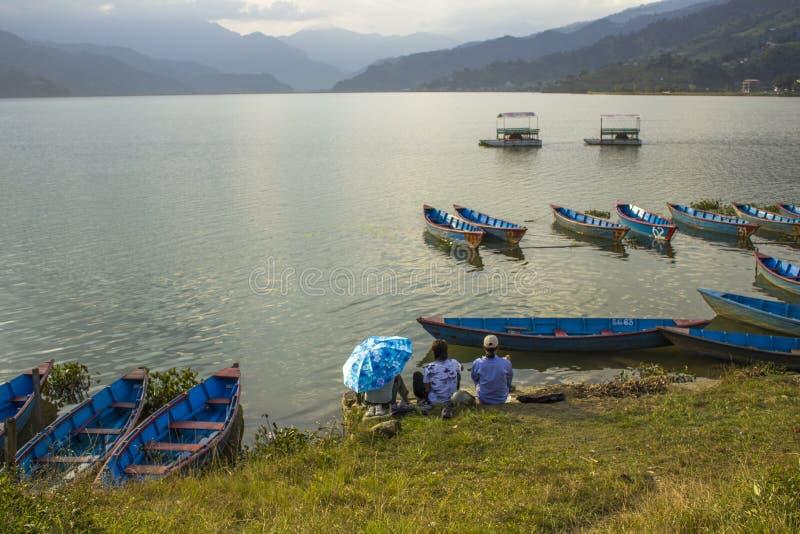 Blaue hölzerne Boote und Katamaran auf dem Wasser Ruderboote auf dem See gegen den Hintergrund von grünen Bergen Kerle unter lizenzfreies stockfoto