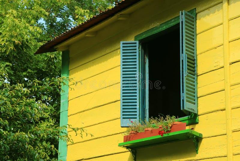 Blaue hölzerne Fensterfensterläden auf klarem gelbem Haus unter grünem Laub im Sonnenlicht lizenzfreie stockfotografie