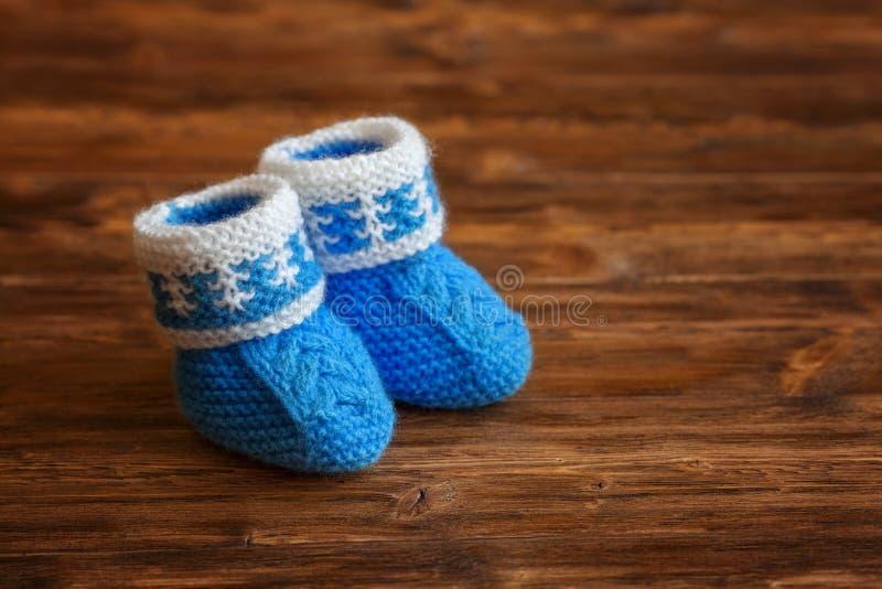 Blaue handgemachte Häkelarbeitbabybeuten auf hölzernem Hintergrund, copyspace lizenzfreie stockfotos