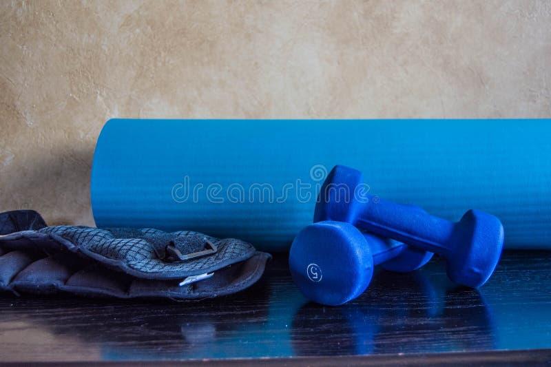 Blaue Hanteln-, Matten- und Knöchelgewichte für das excersie gestapelt auf einander stockfotos