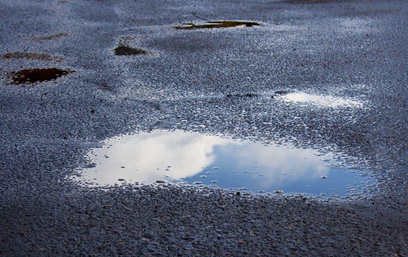 Blaue Himmel in der Regen-Pfütze stockbild