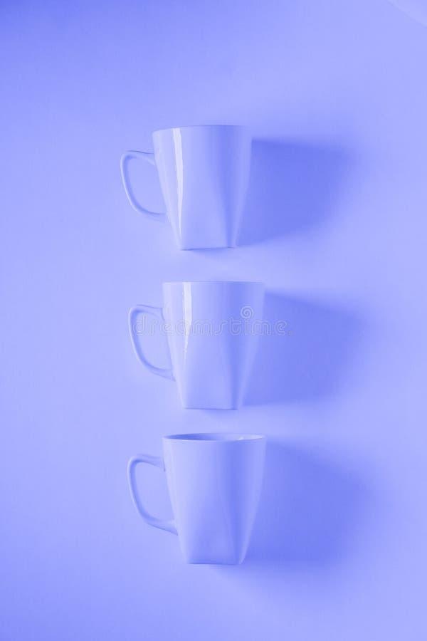 3 blaue Kaffeetassen auf blauem Hintergrund in einer vertikalen Reihe mit leerem copyspace lizenzfreie stockfotografie