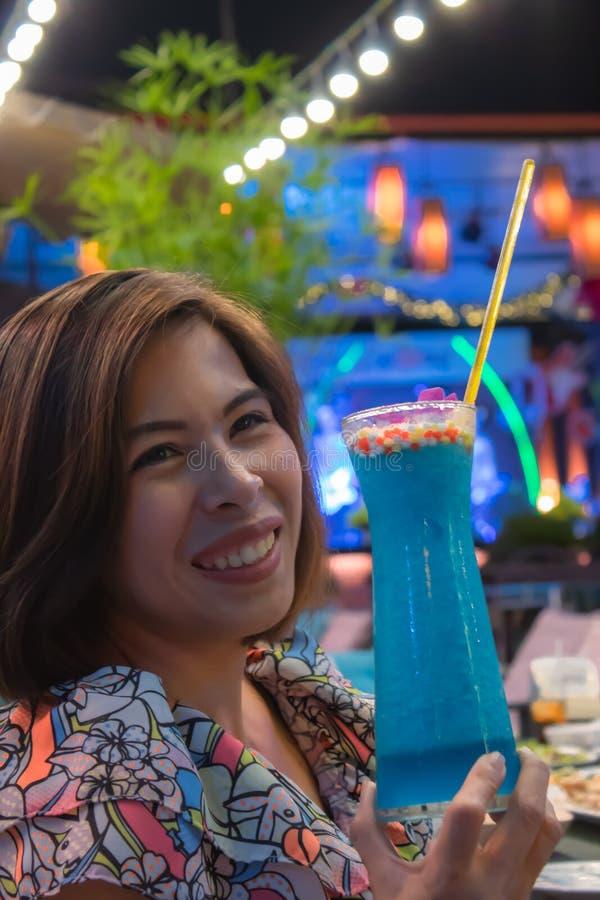 Blaue Kamikazekälte im Glas auf einer Handfrau stockbild