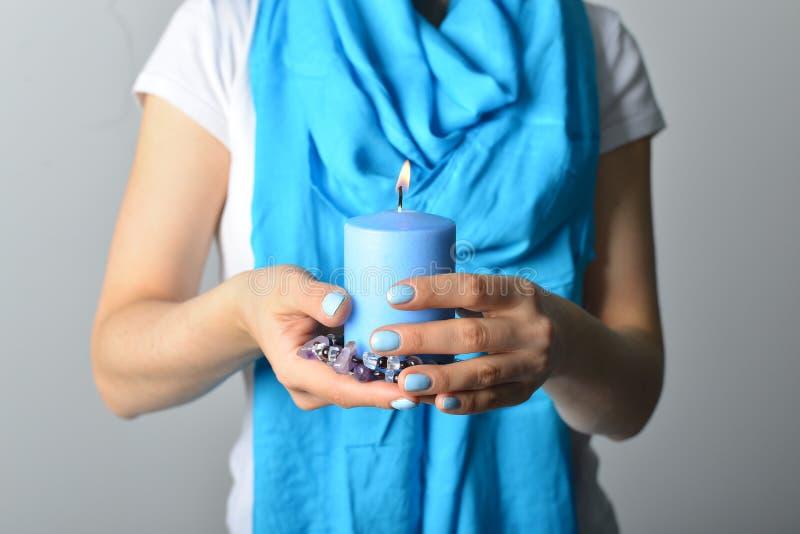 Blaue Kerze in den Händen lizenzfreie stockfotos