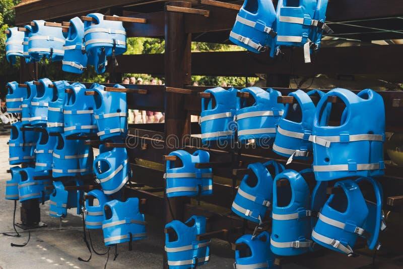 Blaue kleine Schwimmwesten hängen an der Wand mit Haken im waterpark lizenzfreie stockfotos