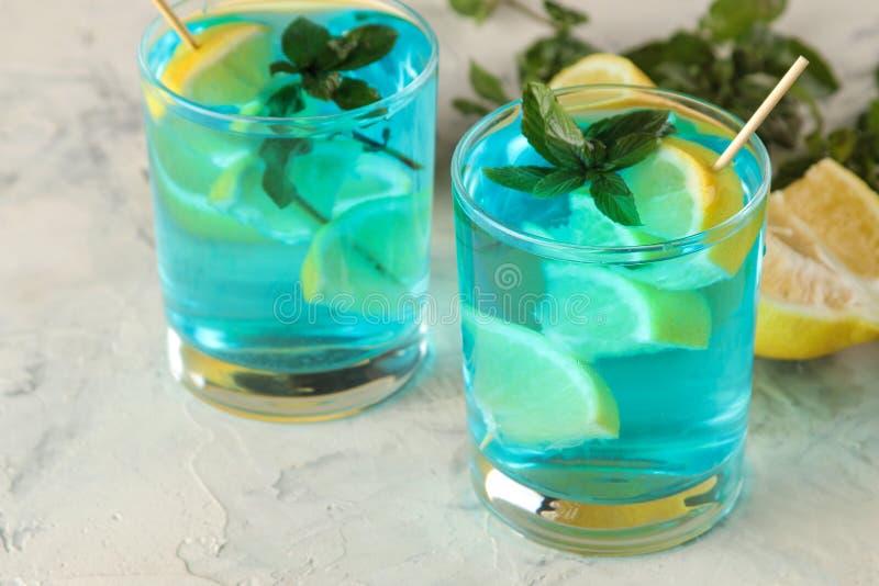 Blaue Lagune des Cocktails in einem Cocktailglas mit Zitrone und Minze auf einer hellen Tabelle in der Bar kühles Sommercocktail lizenzfreies stockfoto