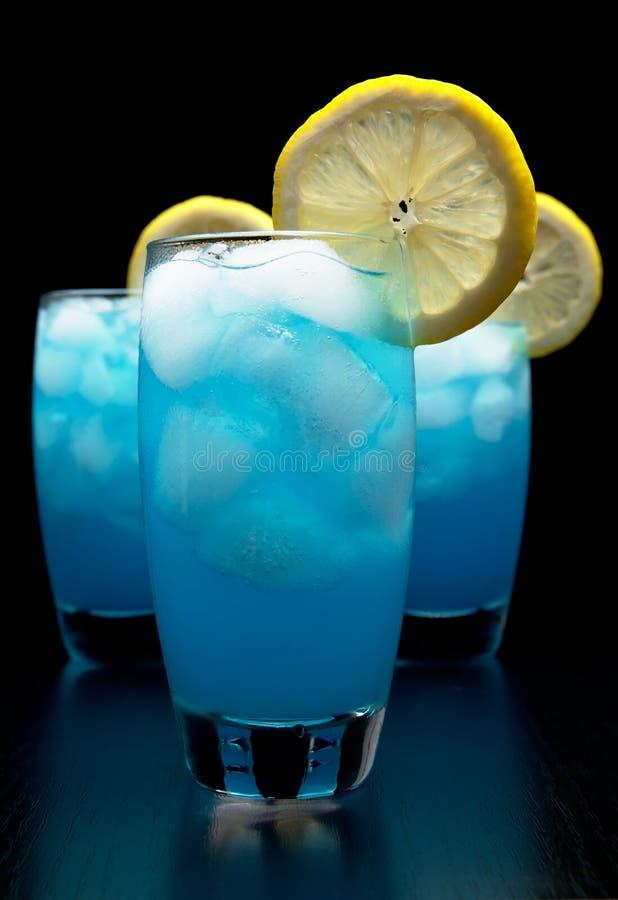 Blaue Lagunencocktails mit Eiswürfeln, Zitrone auf Schwarzem lizenzfreies stockbild