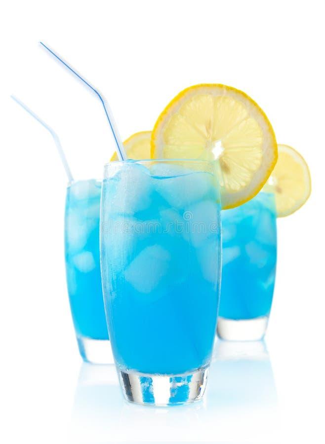 Blaue Lagunencocktails mit Eisw?rfeln, -zitrone und -stroh auf Wei? stockfotos