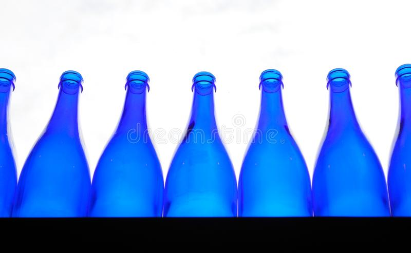 Blaue leere Flaschen richteten auf einem Zähler aus stockfoto