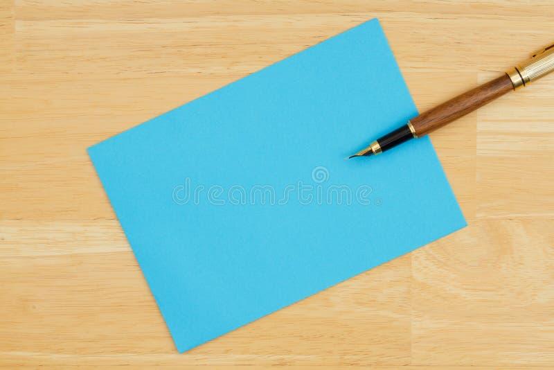 Blaue leere Grußkarte mit einem Stift auf strukturiertem hölzernem Hintergrund stockfoto