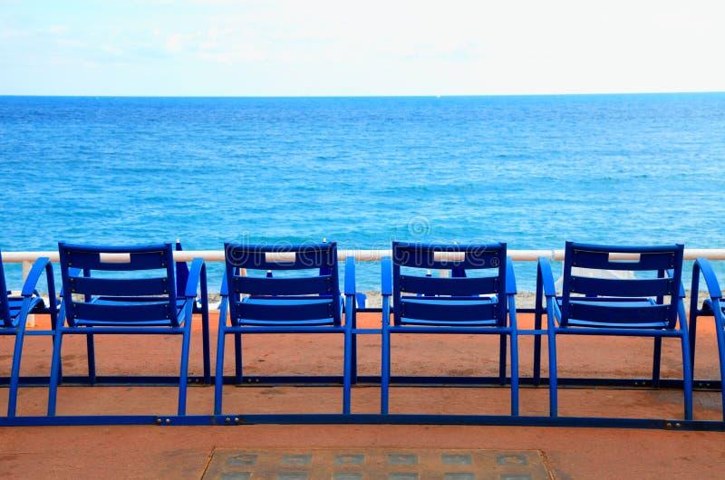 Blaue leere Stühle auf der Seeufergegend, Nizza, Frankreich stockfotos