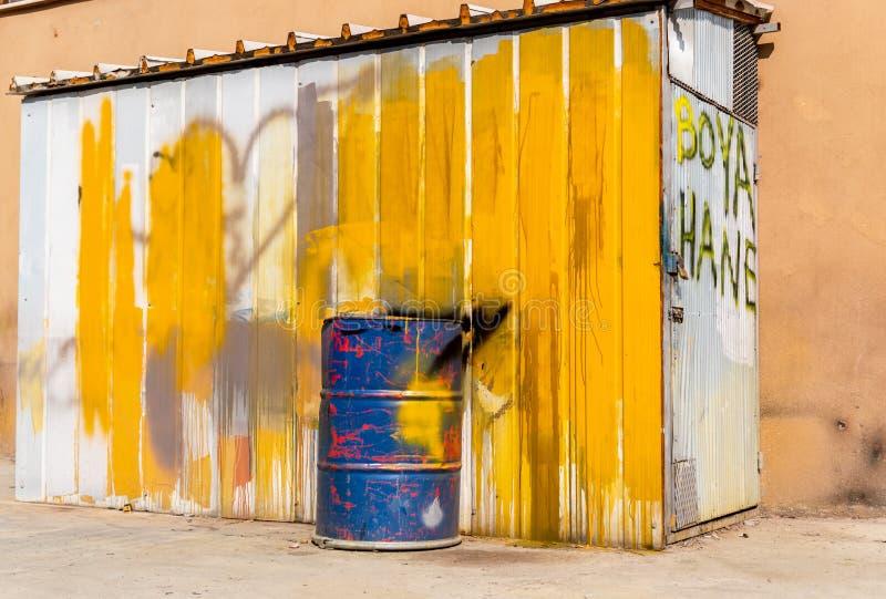 Blaue Metalltrommel vor einer Halle gemalt in weißem und in Gelbem Text auf der Tür: Färbungshaus stockbilder