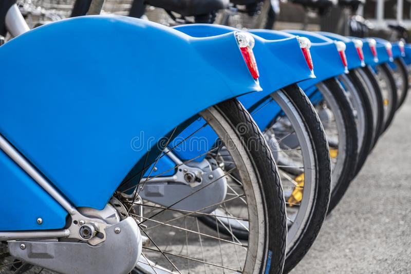 Blaue Mietfahrräder in Folge stockbild