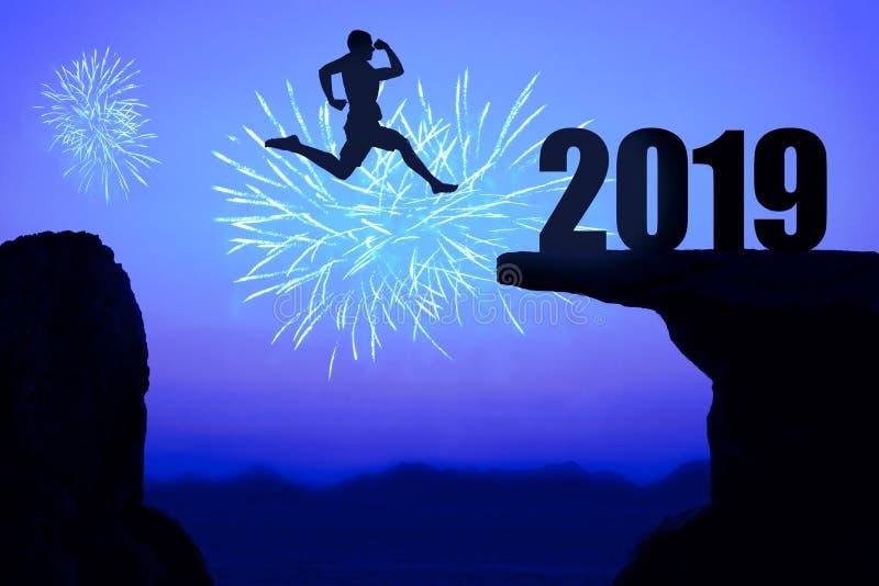 Blaue Nachtfeuerwerke mit Schattenbild des neuen Jahres 2019 und springendem m stockbild