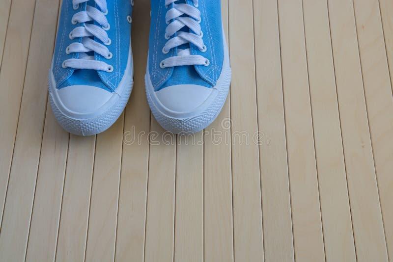 Blaue neue Turnschuhe auf dem hölzernen Hintergrund stockfotos