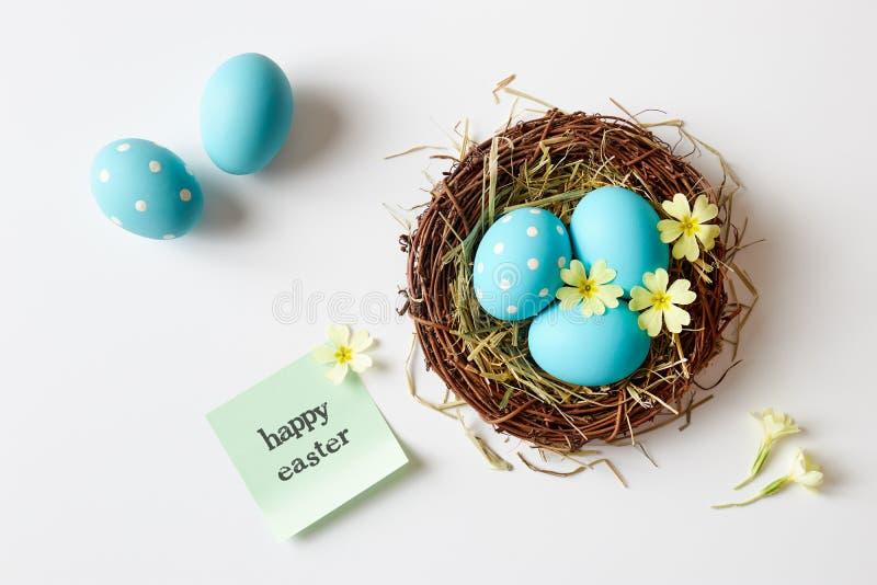 Blaue Ostereier im Nest mit Mitteilung 'fröhlicher Ostern ' stockfotografie