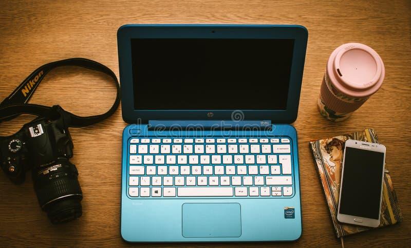Blaue Pferdestärken Netbook neben schwarzer Kamera Nikon Dslr und Weiß Samsung Smartphone auf Buch stockfoto