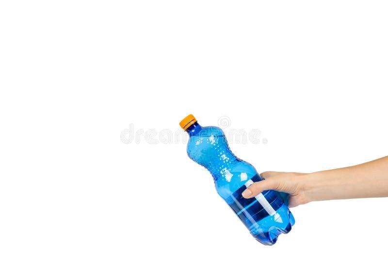 Blaue Plastikwasserflasche mit der orange Kappe, lokalisiert auf weißem Hintergrund, mit der Hand, Kopienraumschablone stockfotografie