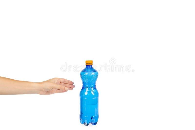 Blaue Plastikwasserflasche mit der orange Kappe, lokalisiert auf weißem Hintergrund, mit der Hand, Kopienraumschablone stockbild