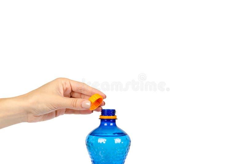 Blaue Plastikwasserflasche mit der orange Kappe, lokalisiert auf weißem Hintergrund, mit der Hand, Kopienraumschablone lizenzfreie stockfotografie