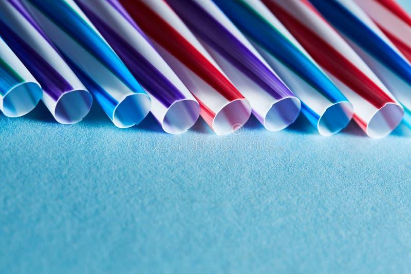 Blaue, purpurrote und rote Plastikstrohe auf einem Hintergrund des blauen Papiers Kopieren Sie Raum für Text stockfotografie